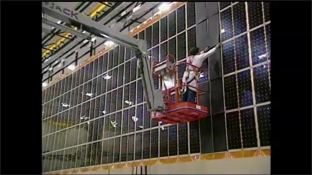 1990s: High angle, space station part moving in lab. Man assembling solar panels.