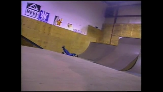 1990s: Indoor skate park.  Men fall off skateboards.