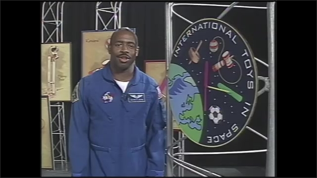 1990s: Astronaut walks among images of toys and International Space Station logo and speaks.