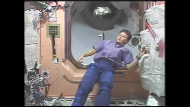 1990s: Astronaut tapes bolt to wooden top. Woman spins bolt and top in zero gravity. Top floats and spins near astronaut on space station.