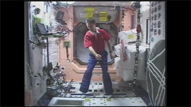 1990s: Astronaut plays with astro jacks toy in zero gravity. Man swings rope with balls on space station.