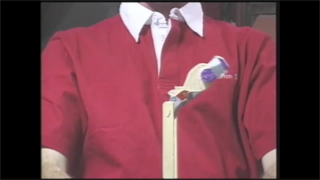 1990s: Woman tapes arms and legs of flipping wooden bear toy. Man squeezes toy and bear spins and flips.