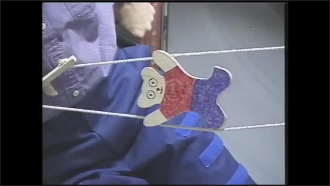 1990s: Hands pull ropes and wooden bear climbs sideways in zero gravity.  Astronauts hold climbing bear toy ropes and work together.