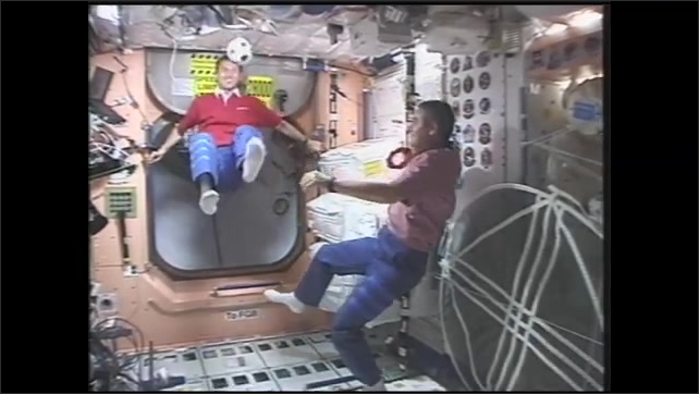 1990s: Astronauts float in zero gravity and kick soccer ball back and forth. Astronaut kicks soccer ball into camera operator.