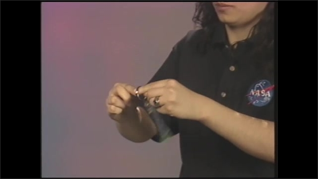 1990s: Girl spins key chain with glitter in hands on sound stage.