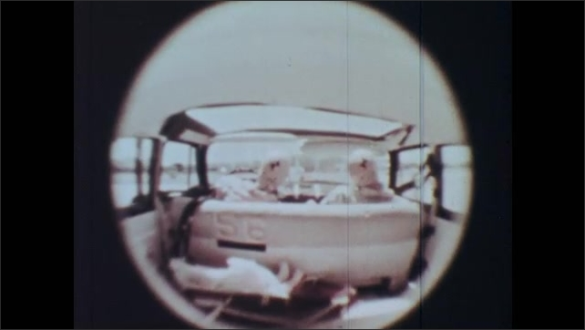 1960s: Interior of crash test dummies in car being hit at a variety of speeds. Crash test dummies and baby bassinet flies around the interior of car.