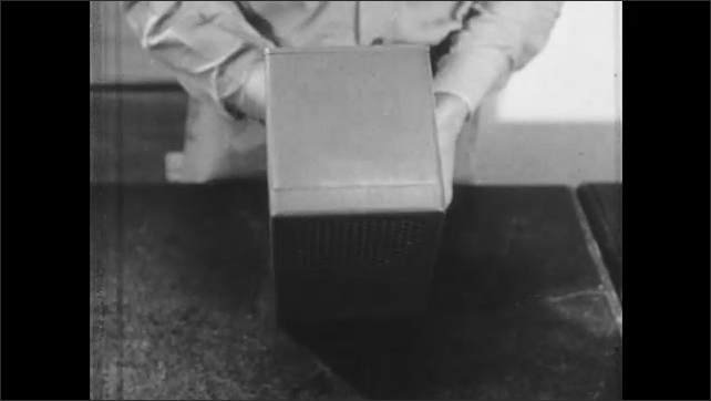1940s: UNITED STATES: man picks up chamber in hands. Gamma ray movement on diagram.