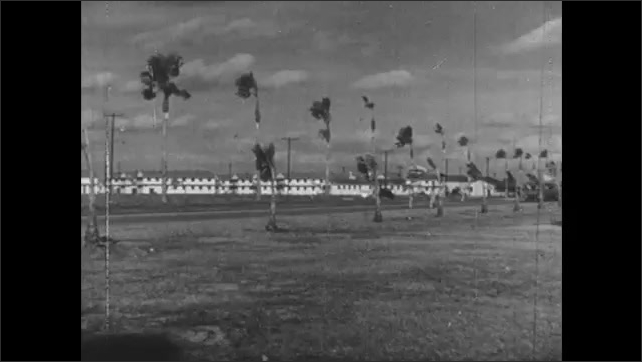 1940s: UNITED STATES: man writes gamma reading in notebook. Cars drive on road. Explosion and clouds. Planes over air force base