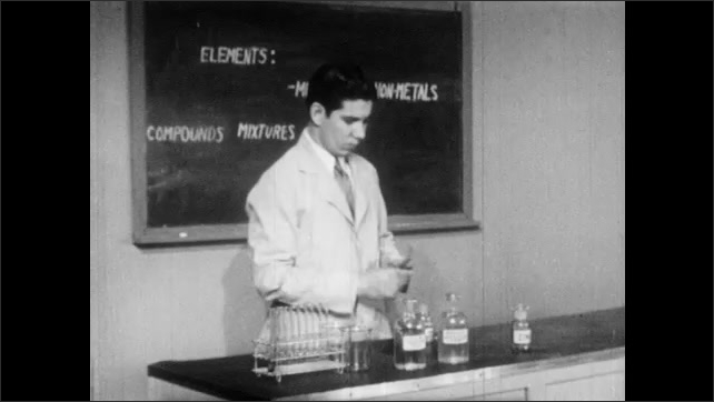 1940s: Scientist unstops and decants Mercuric Oxide into test tube. Scientist holds test tube over Bunsen Burner flame.