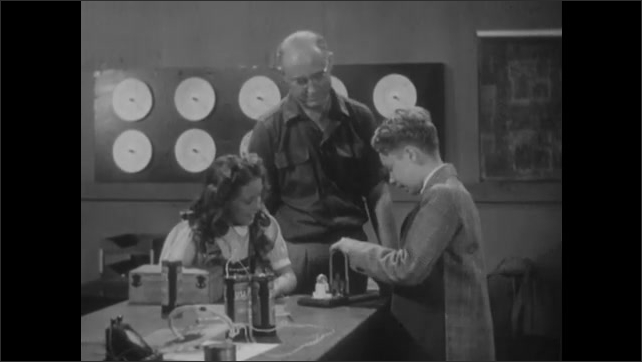 1940s: Needle on meter moves back and forth. Man holds coil of wires in front of magnet as boy and girl watch. Man sets device on desk. Boy turns crank on device and lightbulb lights up.