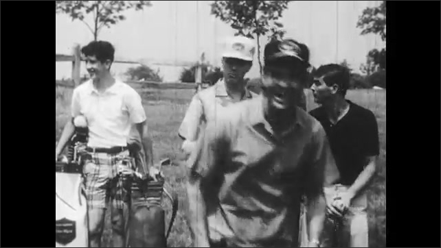 1960s: UNITED STATES: men play golf in summer. Man hits golf ball on green. Men look pleased. Man calls golf player over.