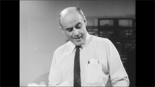 1960s: UNITED STATES: Men report to RADEF facility. Men speak about emergency updates. Men in office work at desk.