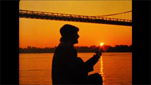 1980s: man in cap sits, sings and plays acoustic guitar near automobile bridge at river in city at sunset. seagulls fly over ocean waves. fog nests around hilly forest in countryside.