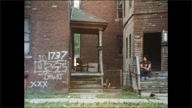 1980s: men sit on steps of abandoned apartment building. broken windows and doors of decaying housing. man relaxes on broken steps of house. guys, women, boys and girls line up on streets near gutter.