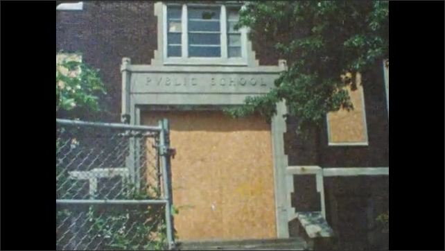 1980s: houses with chipped paint. boys sit on car trunk and smoke cigarettes. boards block entrance to public school. kids play on stoop and soak in plastic pool on sidewalk near buildings in city.