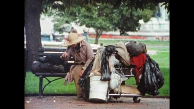 1980s: man spoons food and eats from styrofoam cup on sidewalk. woman in hat sits on bench and smokes cigarette near supermarket full of garbage bags and clothes in park. guy pushes buggy down street.