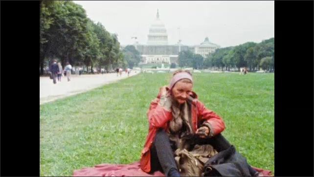 1980s: men sit and stare. woman stands on porch and stairs. lady sits on lawn near US Capitol Building and pulls back raincoat hood. guy holds acoustic guitar and watches nearby river and bridge.