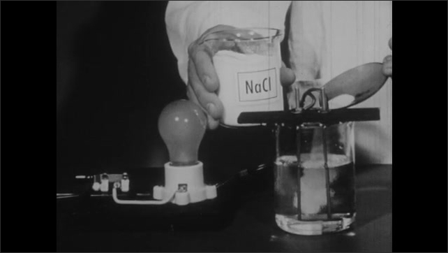 1950s: Flames flicker around dish. Wires protrude from dish. Light bulb attached to wires, glows. Man scoops salt into beaker of water, light bulb attached to beaker turns on.