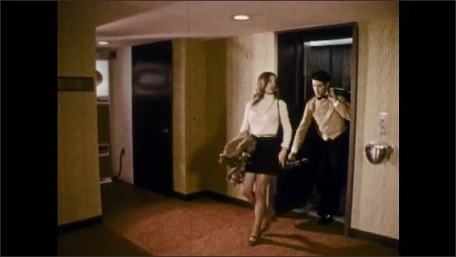 1970s: A taxi pulls up to hotel registration and a doorman opens the door. Hotel employees check in guests, carry luggage, close curtains, turn down bed, and count towels.