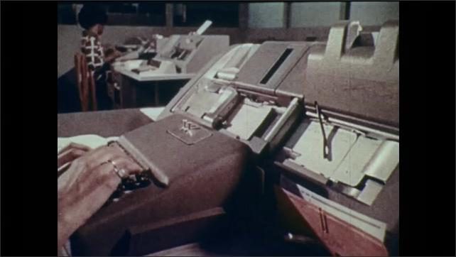 1970s: UNITED STATES: students sit at desks. Animated keyboard. Animated lady at desk. Lady loads typewriter