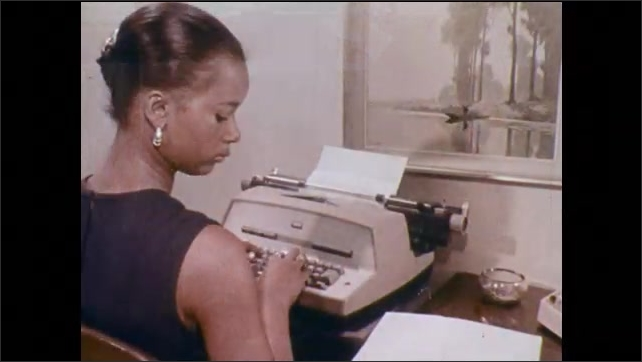1970s: UNITED STATES: lady writes notes. Man in uniform works at desk. Lady types on typewriter. Close up of typing on typewriter