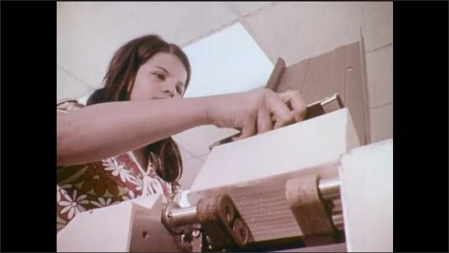 1970s: UNITED STATES: tape reels spin on machine. Close up of lady