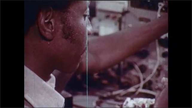 1970s: Man takes notes while looking at circuit board. Man solders circuits under magnifying glass. Man adjusts dial, uses tool. Car enters garage, garage door is electronically-opened.