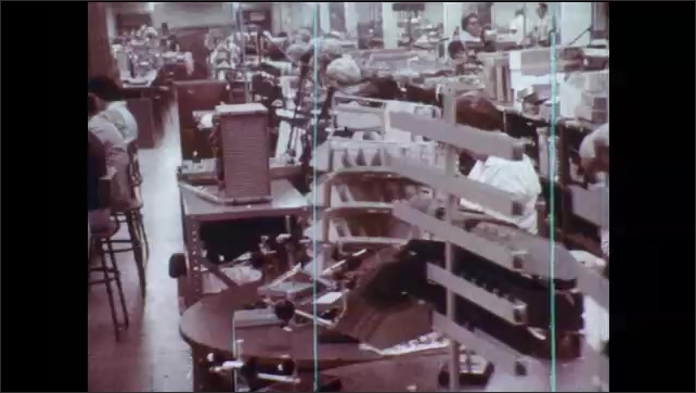 1970s: Man adjusts dials. Metal sheet emerges from hot furnace. Milk bottling plant. Refinery station. Electronic manufacturing factory floor. Circuit boards on rotating platform. Workers at factory.