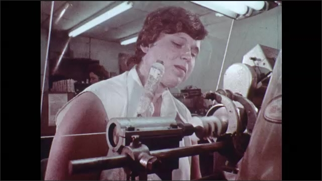 1970s: Man operates glass lathe. Ceramic plant. Woman operates lathe. Metal sheets welded together. Hand coils wire around metal. Man places metal disk on surface. Components sprayed with liquid.