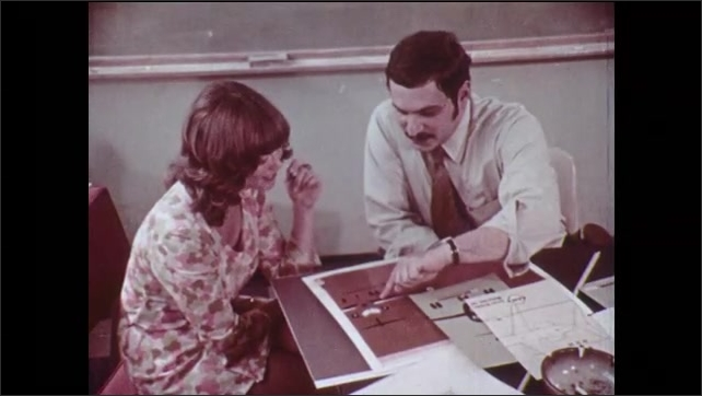 1970s: Man speaks. Men at desk. Woman sorts files. Man gives presentation. Man and woman look at advertisements. Man on phone takes notes. Woman at work: sorting papers, typing, using computers.