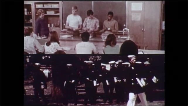 1970s: Men inspect complex blueprint/diagram. Students give presentation in class. ROTC students walk across lawn. Older man shows young man book. Two men work in workshop.