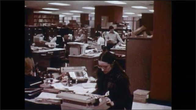 1970s: Woman quickly types on typewriter while reading paper. Office with men and women at work.