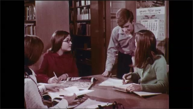 1970s: Woman and man works at machines. Colors. Students seated at table pass around books. Girl speaks to man at desk. Boy joins group of girls at library. Various part time jobs. Classroom.
