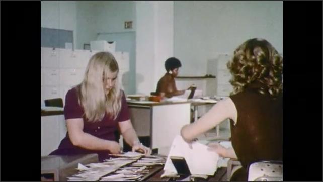 1970s: Insurance company logo. Man talks on phone, walks over to assist people behind counter. Women sort papers in office, people sit at desks. Skyscraper insurance building. Man walks through door.