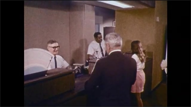 1970s: People work in crowded office. Men work on scientific instruments. Man cooks in kitchen. Men work on jeep. Men and women visit post office. Workers separate letters at post office.