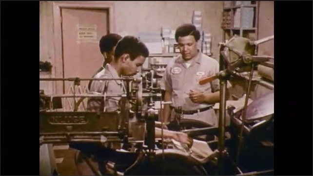 1970s: Men work in assembly factory. Women work at tables. Man works on paperwork.
