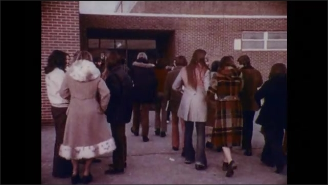 1970s: Male and female students walk into high school.  Teenage girls stand in a group and talk.  Students in hallway.  Girls sit on floor.  Boy chews gum.