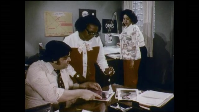 1970s: Man stands to greet other men.  People work together in office.  Employment office.