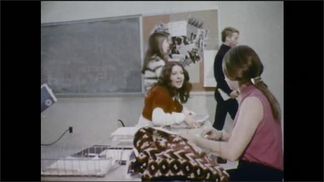 1970s: Teenage boys in bookstore.  Boy opens book.  Students talk with teachers.  Family sits at dinner table.  People sit and talk at employment office.  Woman types.