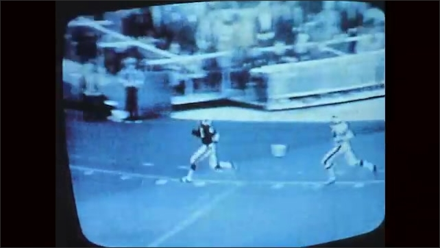1970s: Football game on TV screen, runner with football scores touchdown. Crowd cheers, waving pom-poms.