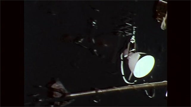 1970s: Man rides motorcycle through parked cars. Studio hanging lights. Man swivels television camera. Camera lens.
