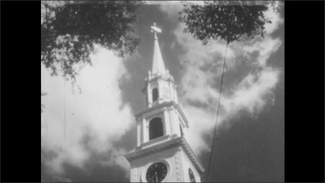 1940s: Church steeple stands among trees. Church steeple reaches to sky. Boy rides bike past homes and delivers newspapers.