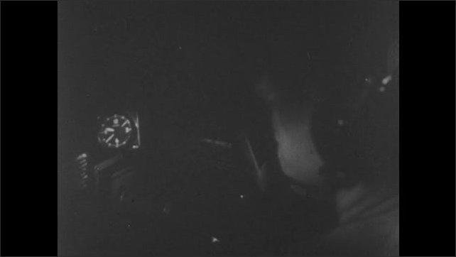 1940s: Second hand on clock moves in plane console. Navy pilots sit in cockpit of plane. Squadron of fighter planes fly at night.