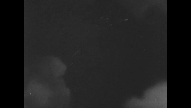 1940s: Gunner smiles and straightens in seat. Pilot looks around cockpit and shouts into radio. Clouds roll by beneath bomber. Pilot speaks into handset.