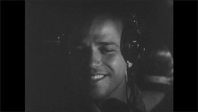 1940s: Tail gunner looks from cockpit. Gunner smiles and speaks. Pilot looks around cockpit. Squadron dives to attack enemy ships.
