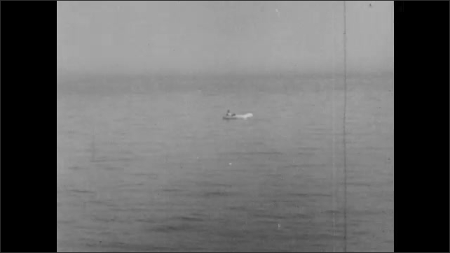 1940s: Ocean vista. Small inflatable lifeboat bobs in ocean. Men lay in lifeboat and talk to each other.