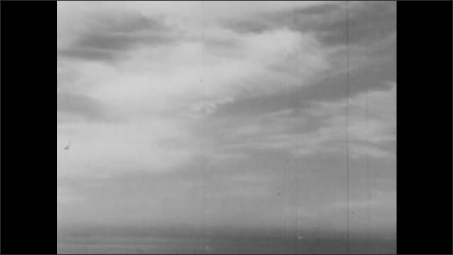 1940s: Man sits up in lifeboat and speaks. Man looks up to sky. Thin clouds in sky. Injured man looks up to sky and speaks.