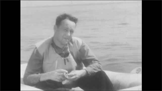 1940s: Man lies on inflatable life raft and speaks. Navy pilot leans on raft and responds.