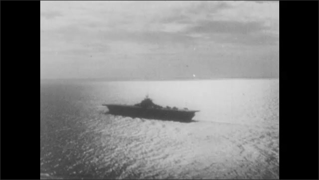 1940s: Man smiles and looks around turret gunner cockpit. Aircraft carrier moves through ocean waters. Plane lands on deck of ship.