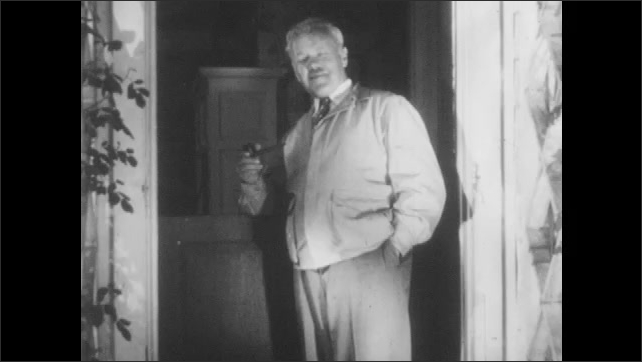 1940s: Man stands in doorway of house and smokes pipe. Man stands in doorway and talks to self. Newspaper and dog sit at man's feet. Bi-line on newspaper.